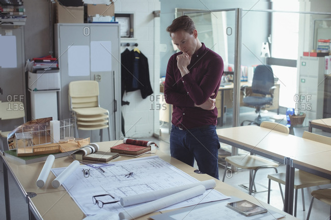 Thoughtful architect looking at blueprint in studio
