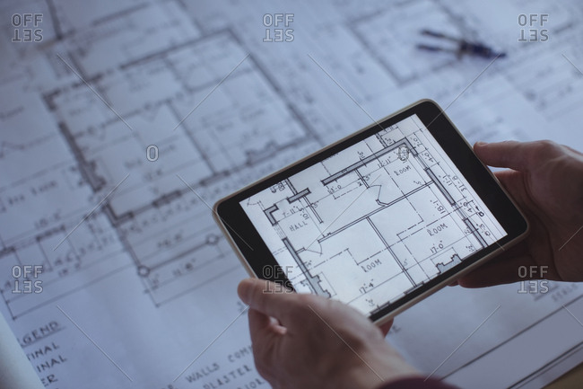 Architect using digital tablet at table in studio