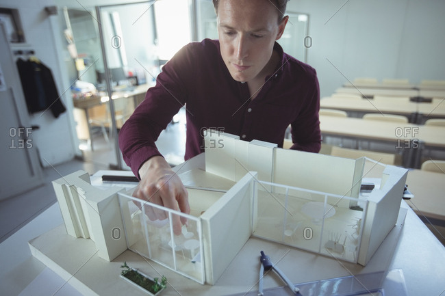 Architect working on house sample in studio