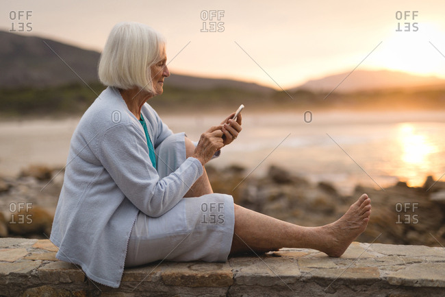 Senior woman sitting on wall and using mobile phone at beach during sunset