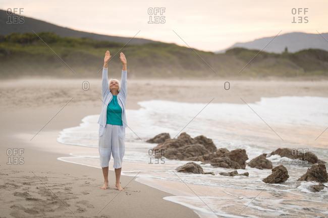 Healthy senior woman exercise on beach during dusk