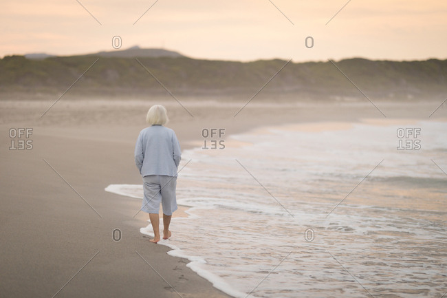 Rear view of senior woman walking on the beach at dusk