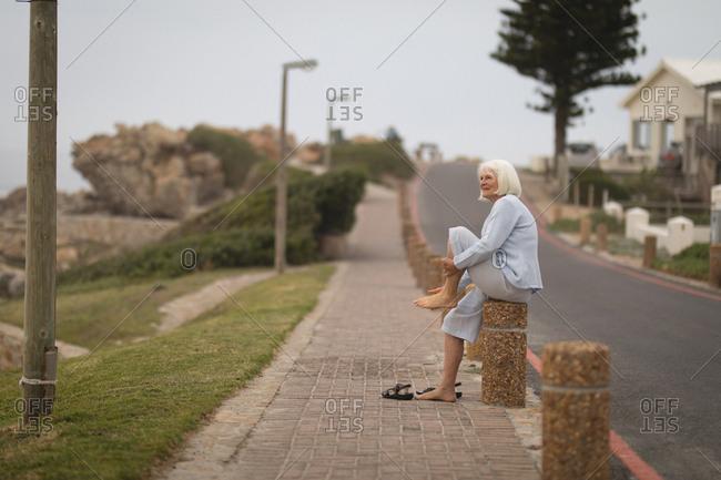 Thoughtful senior woman sitting on bollard
