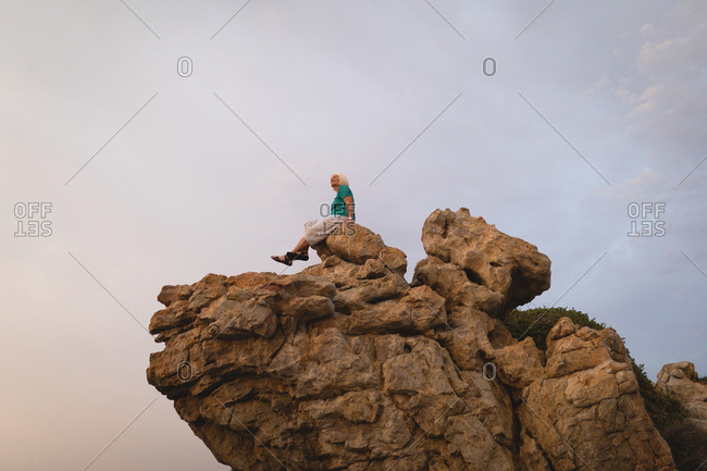 Senior woman sitting on top of cliff at dusk