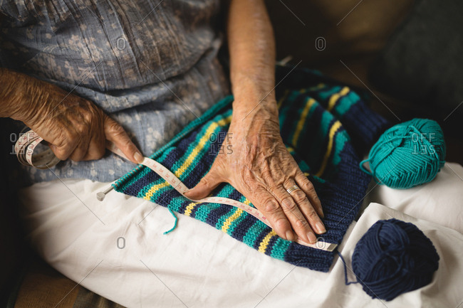 Senior woman measuring knitted sweater at home