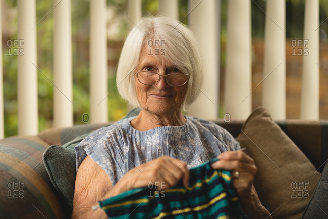 Portrait of senior woman knitting wool in living room at home