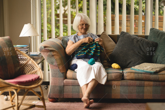 Senior woman knitting wool in living room at home