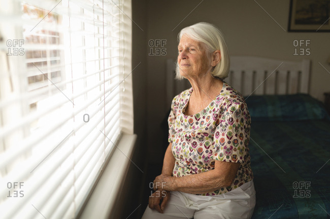 Thoughtful senior woman looking out from window at home