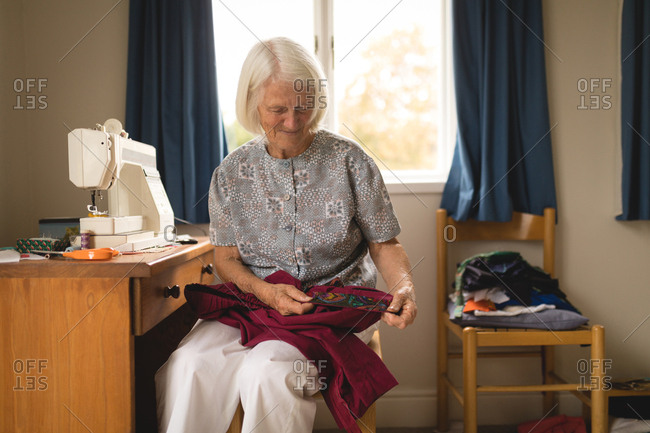 Senior woman looking at sweater in home