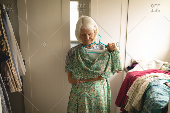 Senior woman holding clothes at home