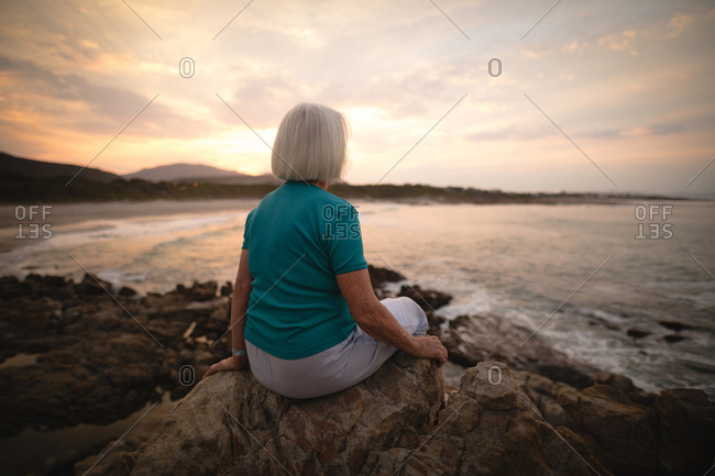 Senior woman sitting on seaside rocks during dusk