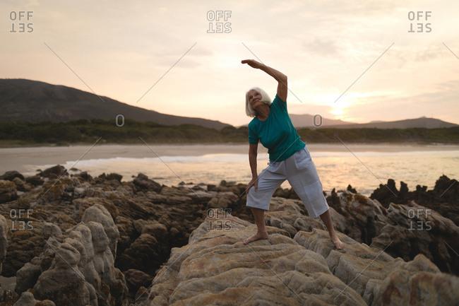 Senior woman doing exercise on seaside rocks during sunset