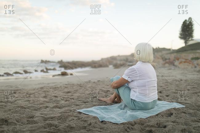 Rare view of senior woman sitting on the beach