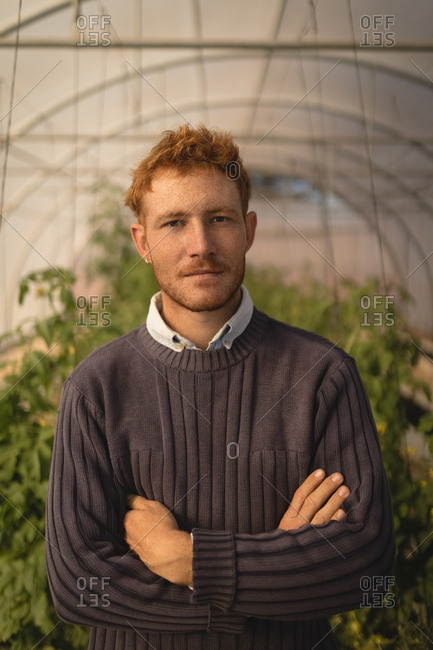Portrait of farmer standing with arms crossed in greenhouse