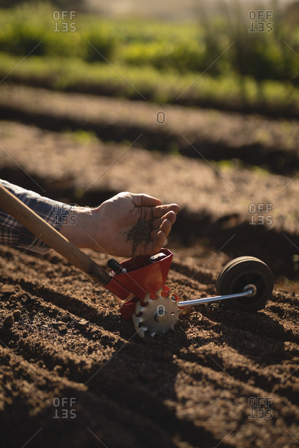 Farmer putting seeds in hand tool on a sunny day