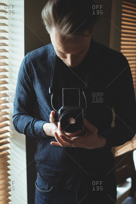 Man holding vintage camera near window at home