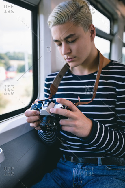 Man reviewing picture on digital camera while travelling in metro