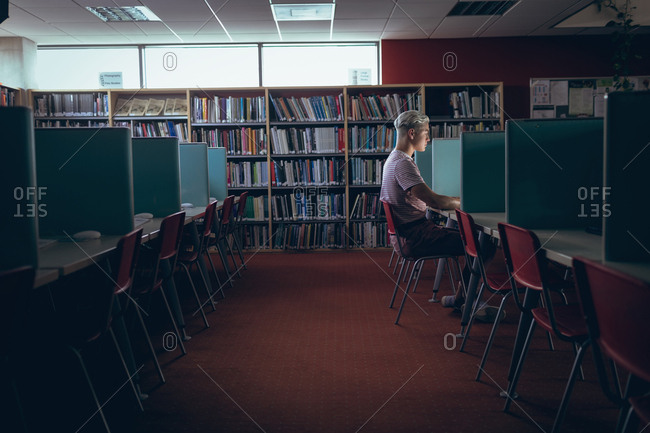 Man studying at desk in library