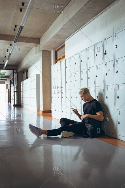 University male student using mobile phone in the corridor of college