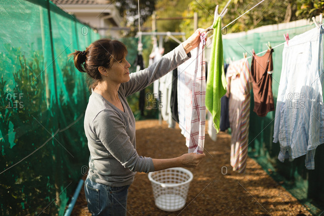 Senior woman hanging laundry on clothes line on a sunny day