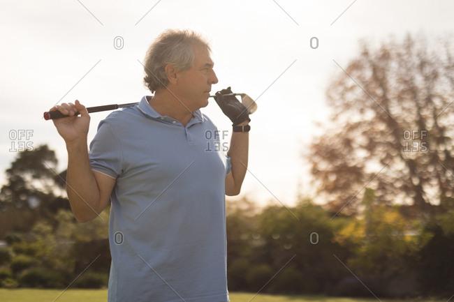 Senior man holding golf stick in golf course