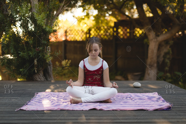 Girl practicing yoga in the park during summer