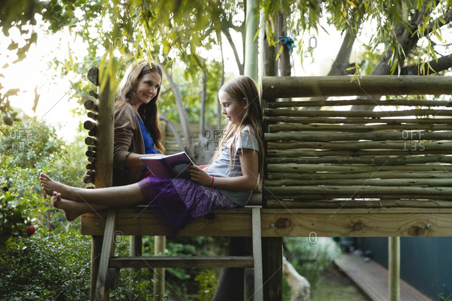 Smiling granddaughter and grandmother reading book on a tree house on a sunny day