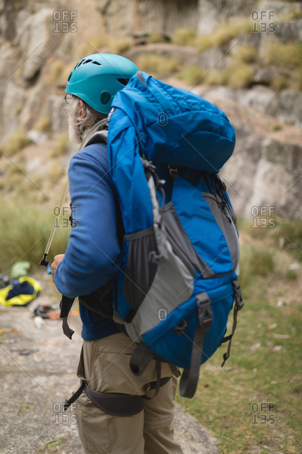 Rear view of man with backpack standing in countryside