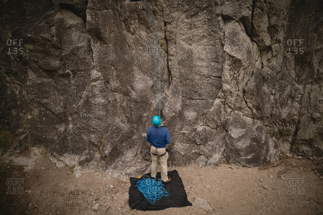 Rear view of man preparing for rock climbing