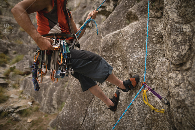 Low section of man with various safety equipment climbing mountain