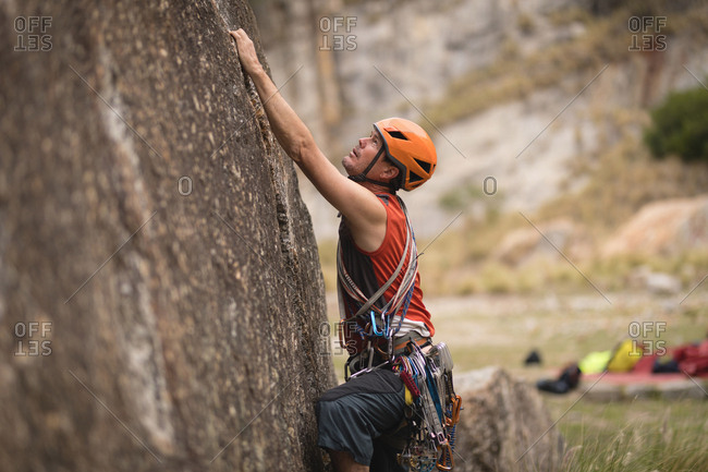 Determined man climbing mountain