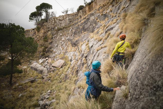 Determined friends climbing a mountain