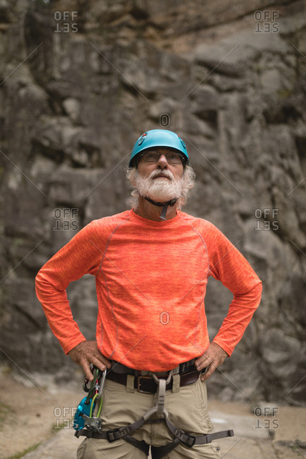 Thoughtful senior man wearing safety equipment during mountaineering