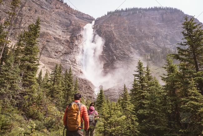 Hiker couple walking towards waterfall in countryside