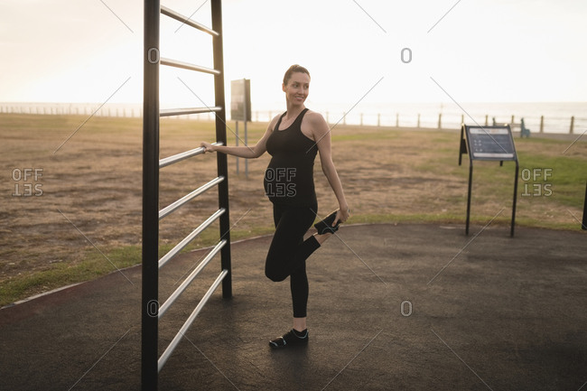 Pregnant woman exercising outdoors on a sunny day