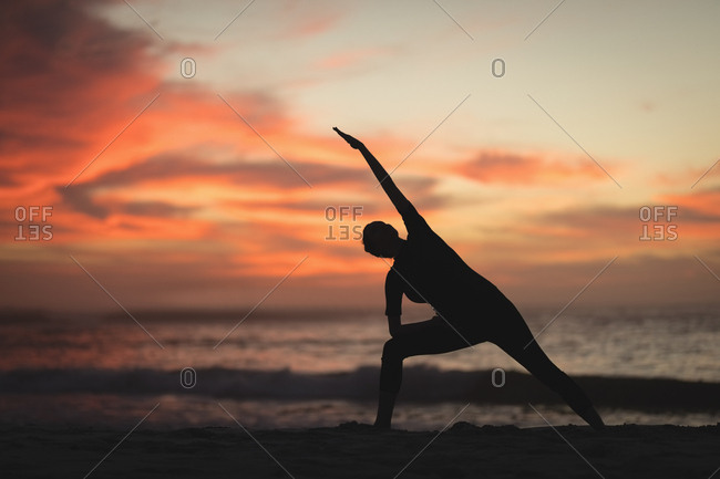 Pregnant woman performing stretching exercise on the beach at dusk