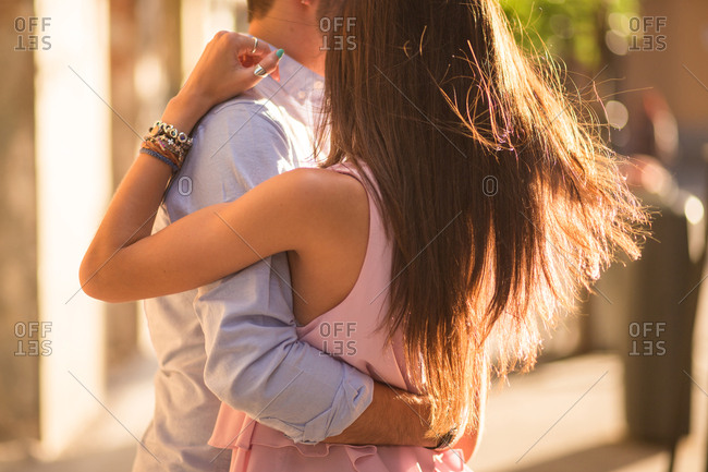 Close-up of unrecognizable hugging couple dancing in sunny street