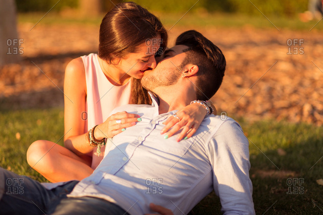 Young couple sharing kiss and hug lying on green grass at sunset