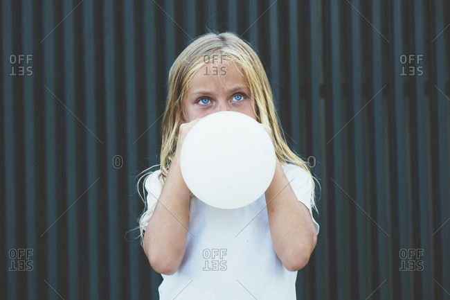 Girl blowing balloon outside