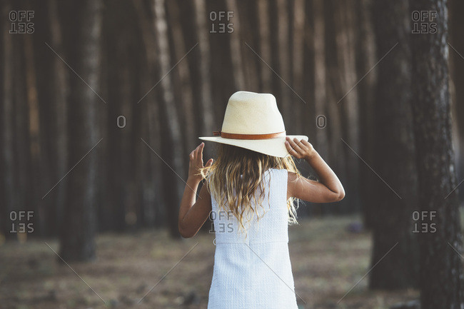 Back view of little girl wearing hat and white dress posing on background of forest