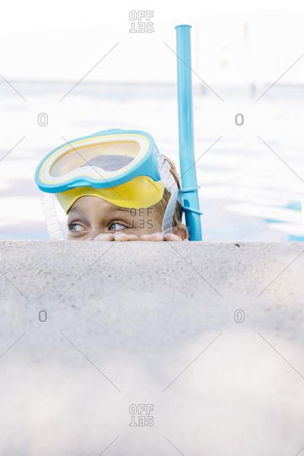 Kid in snorkel mask posing on poolside
