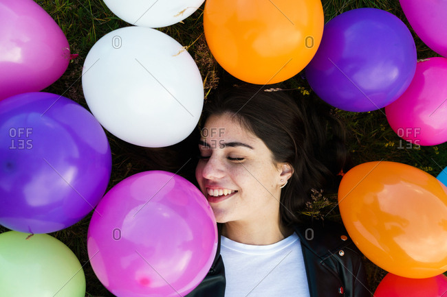Pretty woman lying in balloons