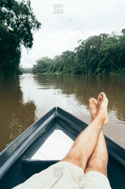 View of incognito male legs relaxing on boat while traveling down river Copy space