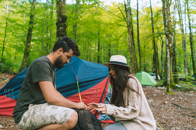 Side view of man and woman with backpack at camp in woods