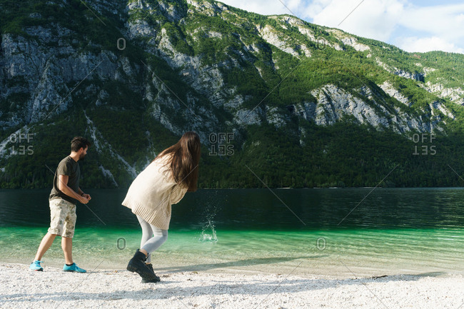 Happy young couple throwing stones to lake standing on shore together