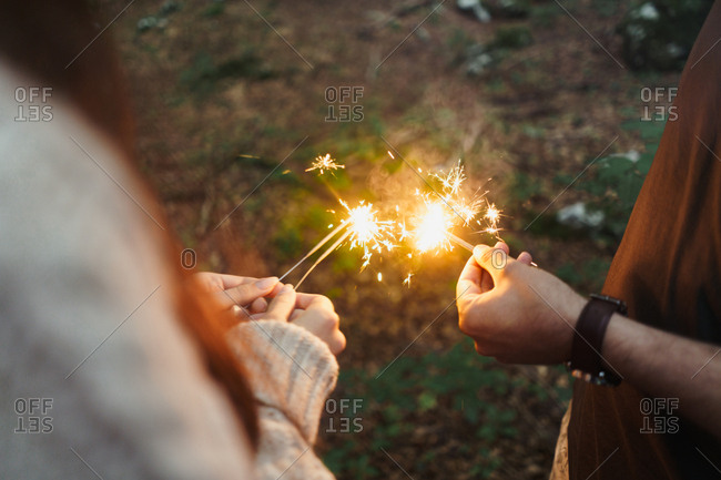 Hands with sparklers in woods