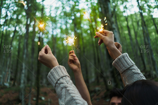 Hands of unrecognizable people holding sparkling lights in the forest
