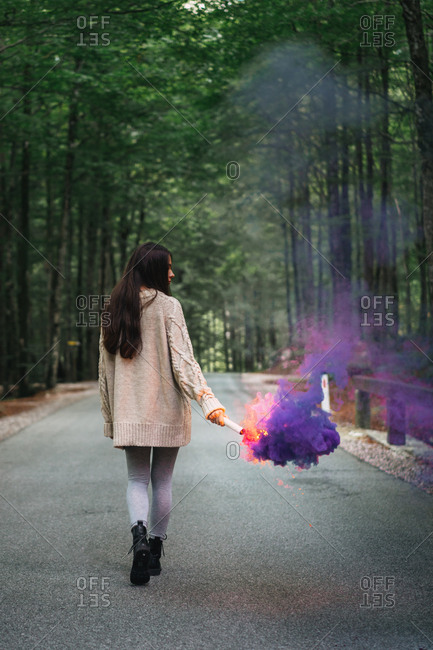 Woman walking with smoke torch