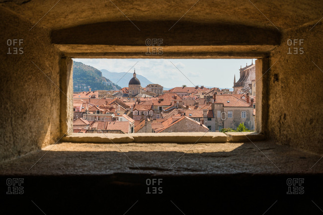 View of beautiful ancient city through window in old stone wall
