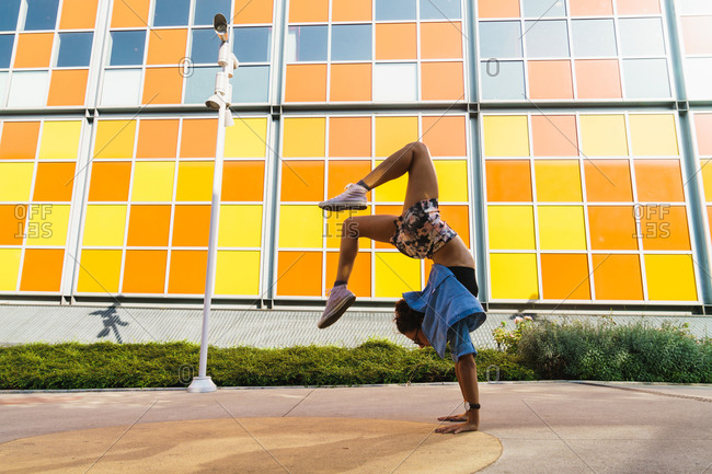 Side view of athletic girl posing in handstand on background of colorful building at street
